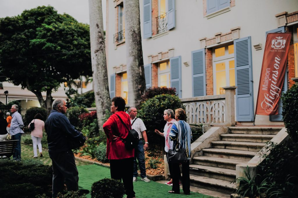 A l'extérieur du bâtiment, un groupe de gens discutent.
